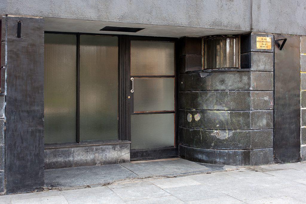 Eingangstür aus Metall mit matten Glasscheiben und einer gerundeten Mauer