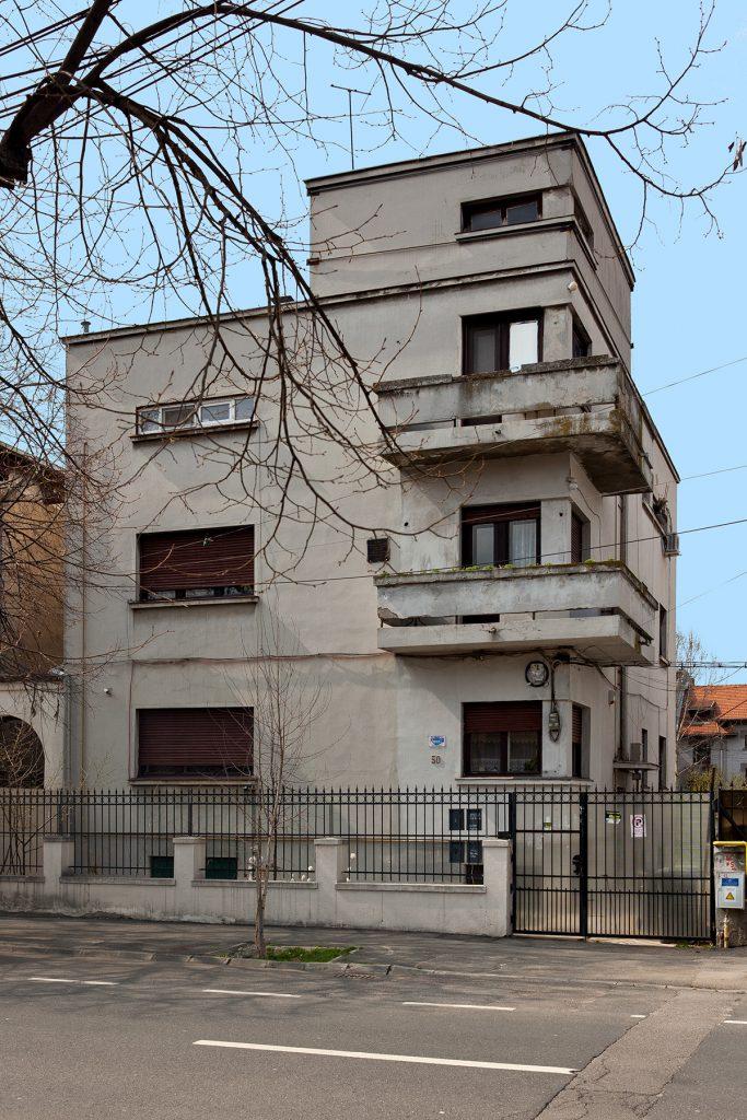 Graues Bauhaus-Wohnaus, dreigeschossig, kubisch mit Balkonen über Eck.