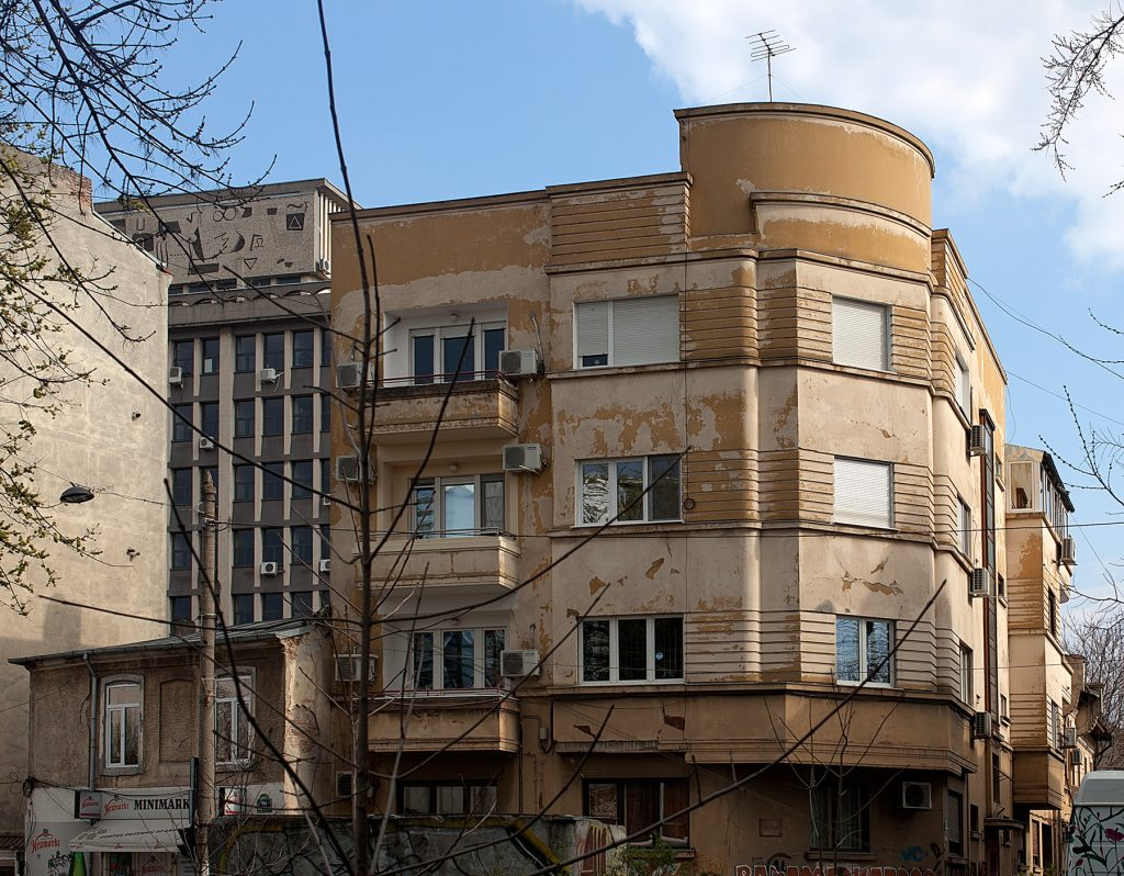 Haus im Bauhaus-Stil mit gekruvter Fassade, ockerne Farbe bröckelt.
