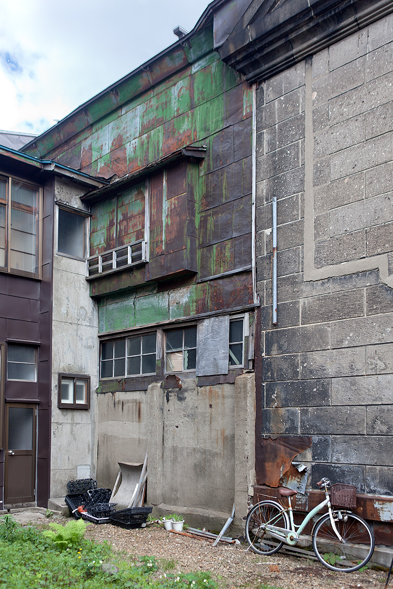 Wand eines Fabrikgebäudes, vor der ein Fahrrad steht