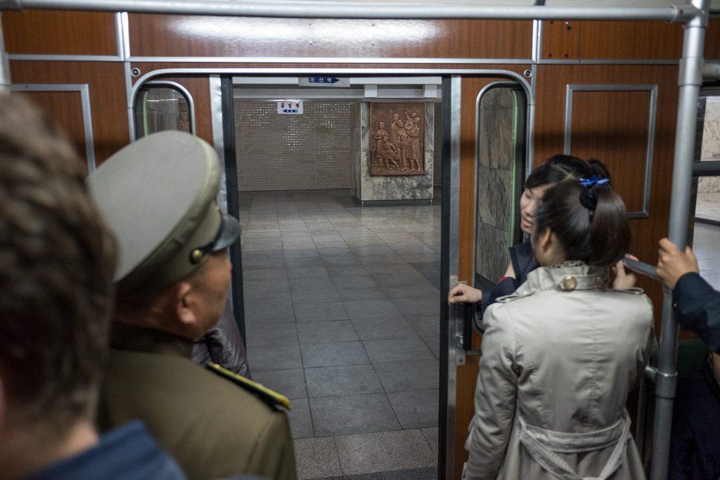 Blick aus einem Metro-Zug auf die gerade sich öffnende Tür und auf Fahrgäste.