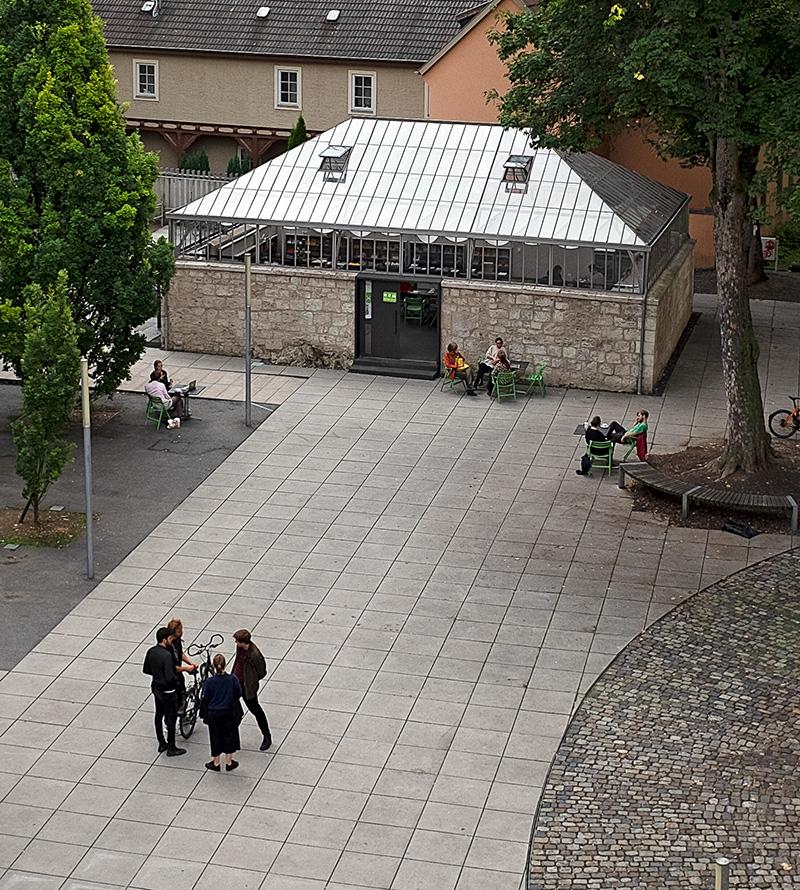 Student*innen vor einem kleinen Gebäude mit Glasdach.
