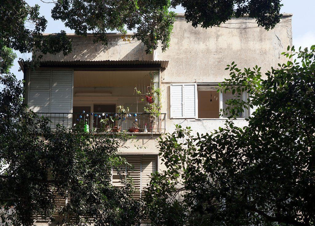 Kubisches Haus der Moderne mit bepflanztem Balkon zu sehen durch Blätter.