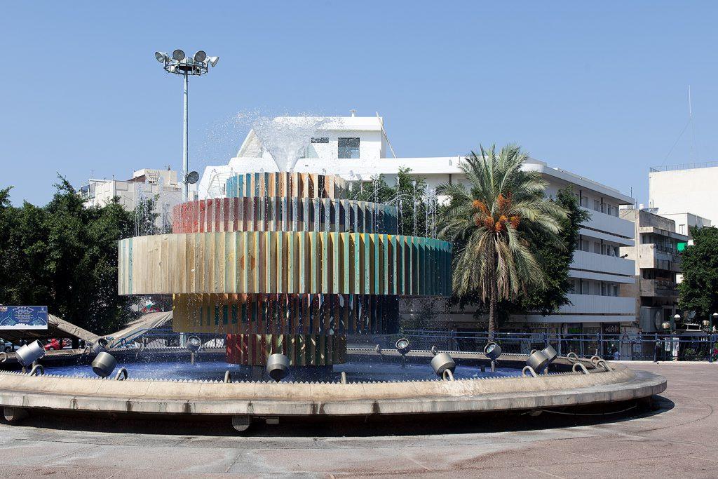 Kinetische Brunnenskulptur auf einem Platz vor weißem Bauhaus.