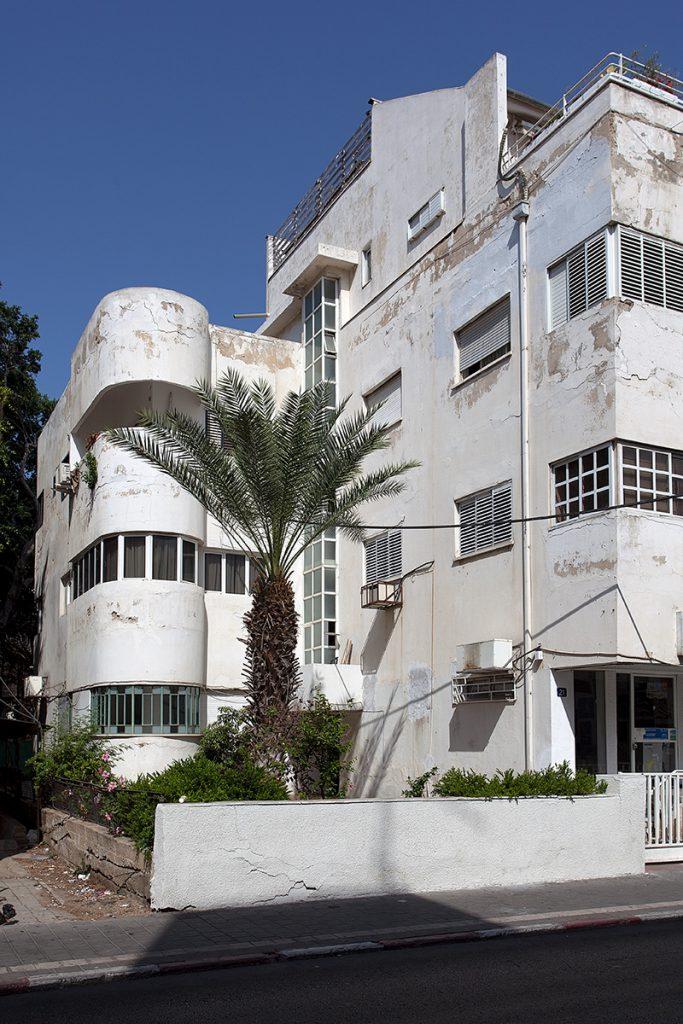 Angeschnittenes weißes Wohnhaus im Bauhaus-Stil. Anbau mit gerundeter Fassade.