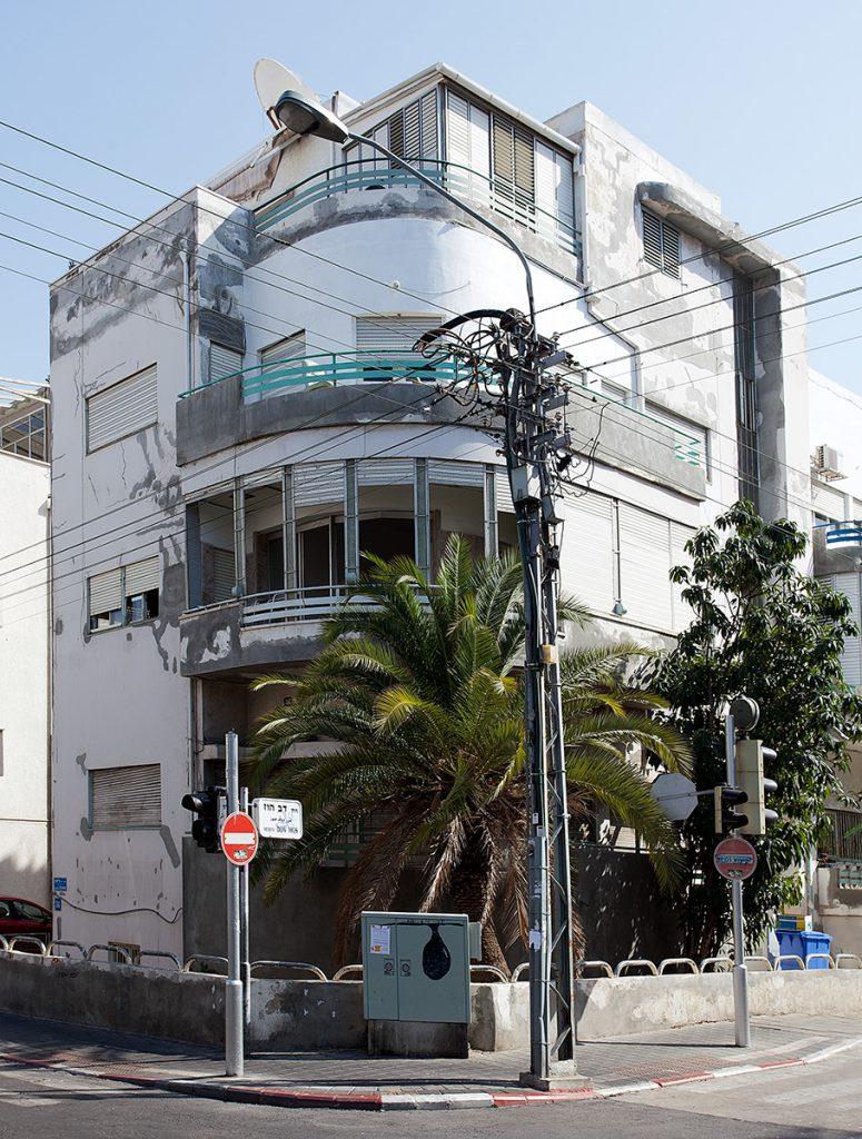 Weißes Eckhaus mit gekurvter Fassade im Bauhaus-Stil. Die Farbe blättert ab.