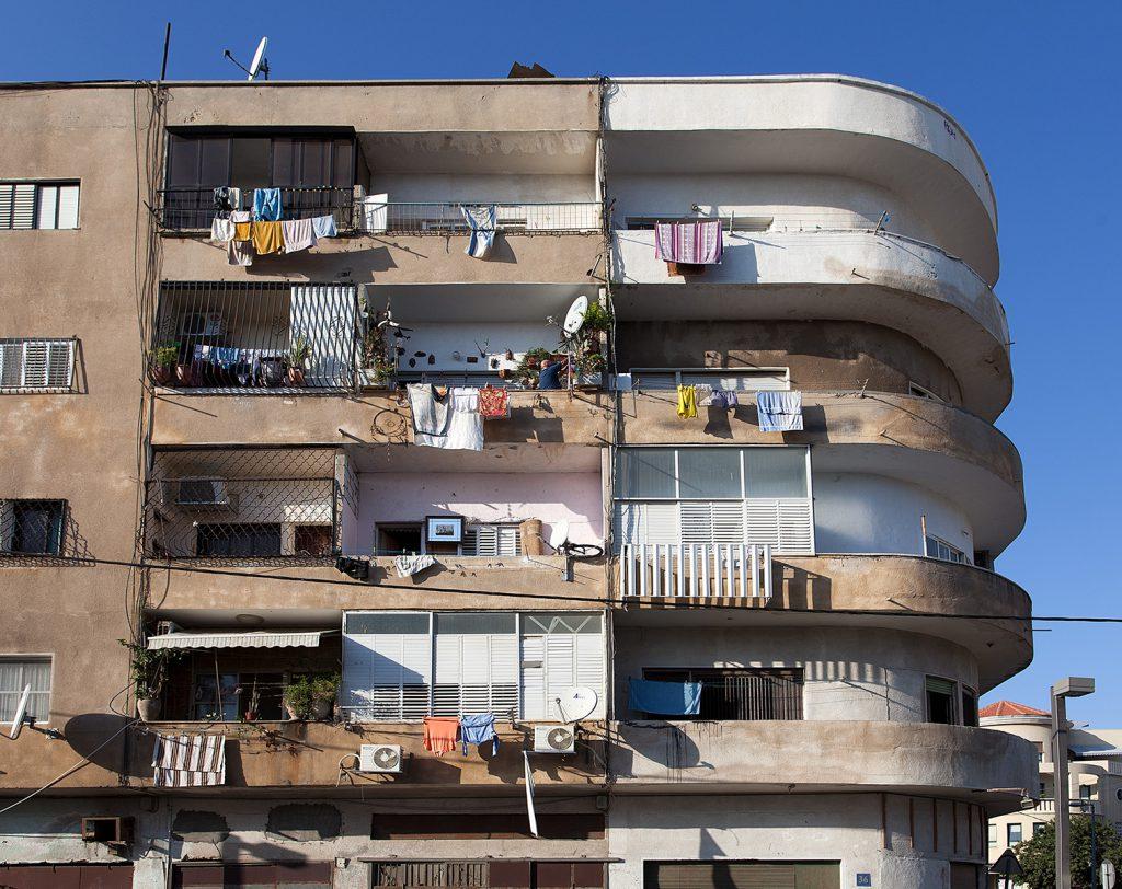 Teil eines mehrgeschossigen Wohnhauses im Bauhaus-Stil mit Wäsche auf den Balkonen.