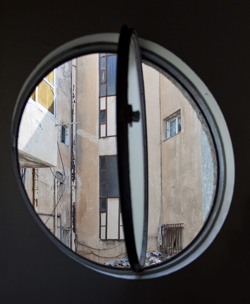 Ausblick durch rundes, geöffnetes Fenster auf eine schrundige Hausfassade mit Fenstern.