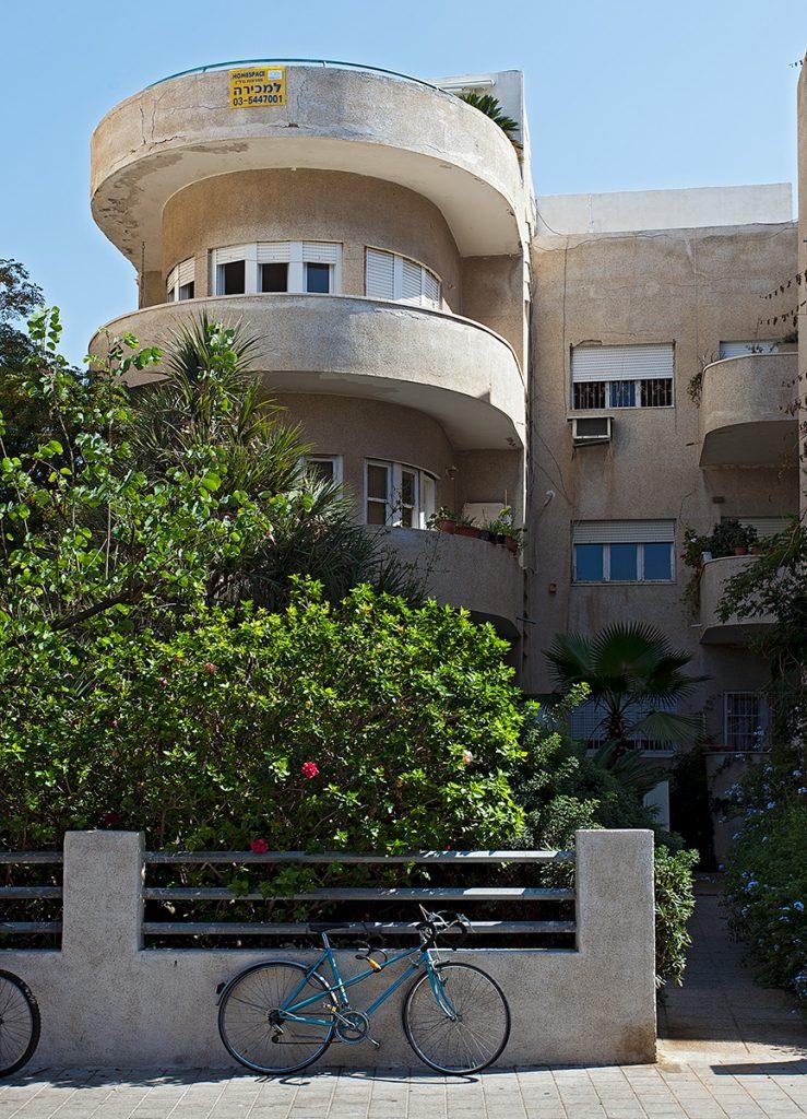 Teil eines ockerfarbenen Hauses im Bauhaus-Stil mit runden Balkonen.