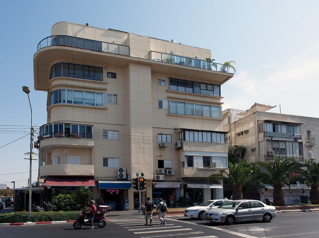 Ockerfarbiges Wohn- und Geschäftshaus im Bauhaus-Stil mit gekurvter Fassade und Balkonen.