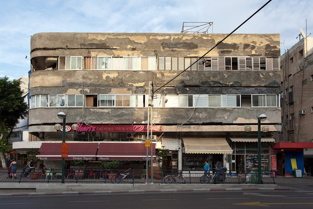 Langgestrecktes Haus mit einer Ladenzeile und darüber zwei Wohnetagen im Bauhaus-Stil.