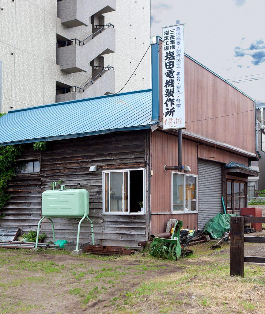 Hausecke mit Werbeschild und zwei Fenstern