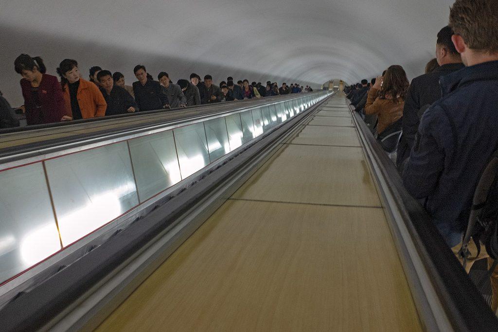 Eine lange Rolltreppe in die Tiefe der Metrostation mit vielen Menschen.