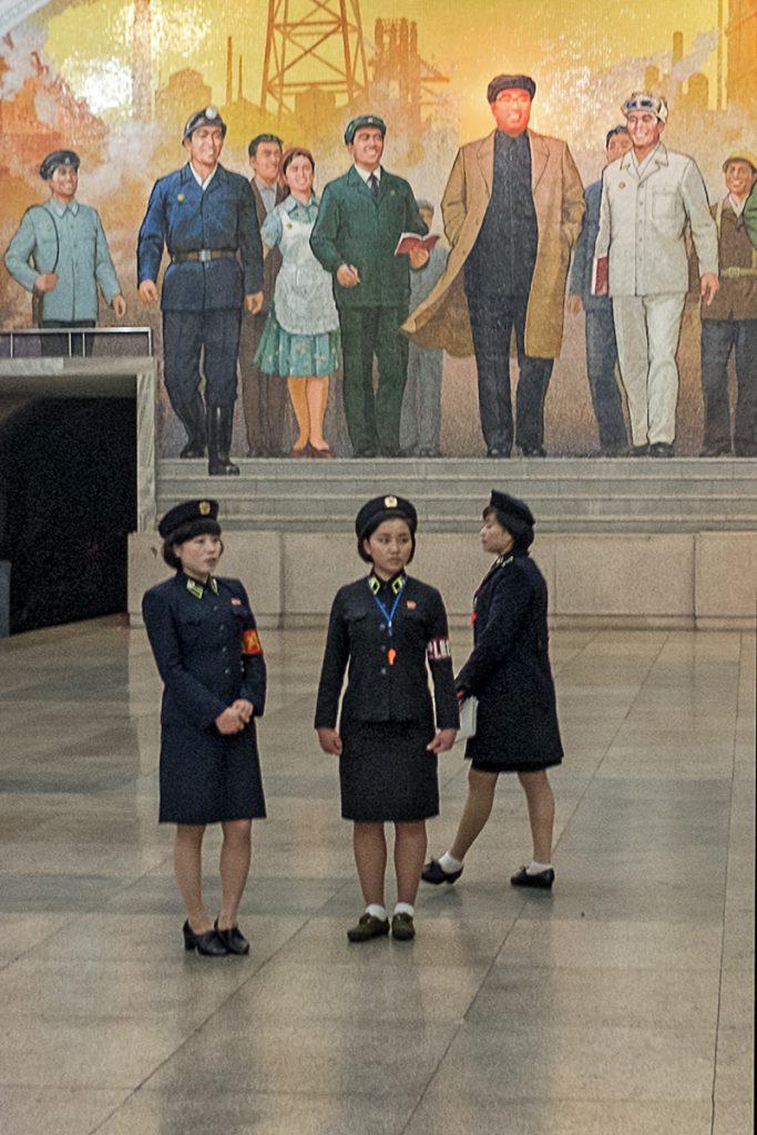 Drei junge Mitarbeiterinnen der Metro vor einem Wandmosaik mit der Darstellung einer Gruppe Menschen.