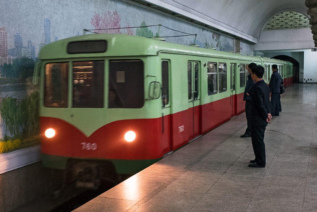 Ein Metro-Zug fährt in die Station, auf den einige Fahrgäste zugehen.