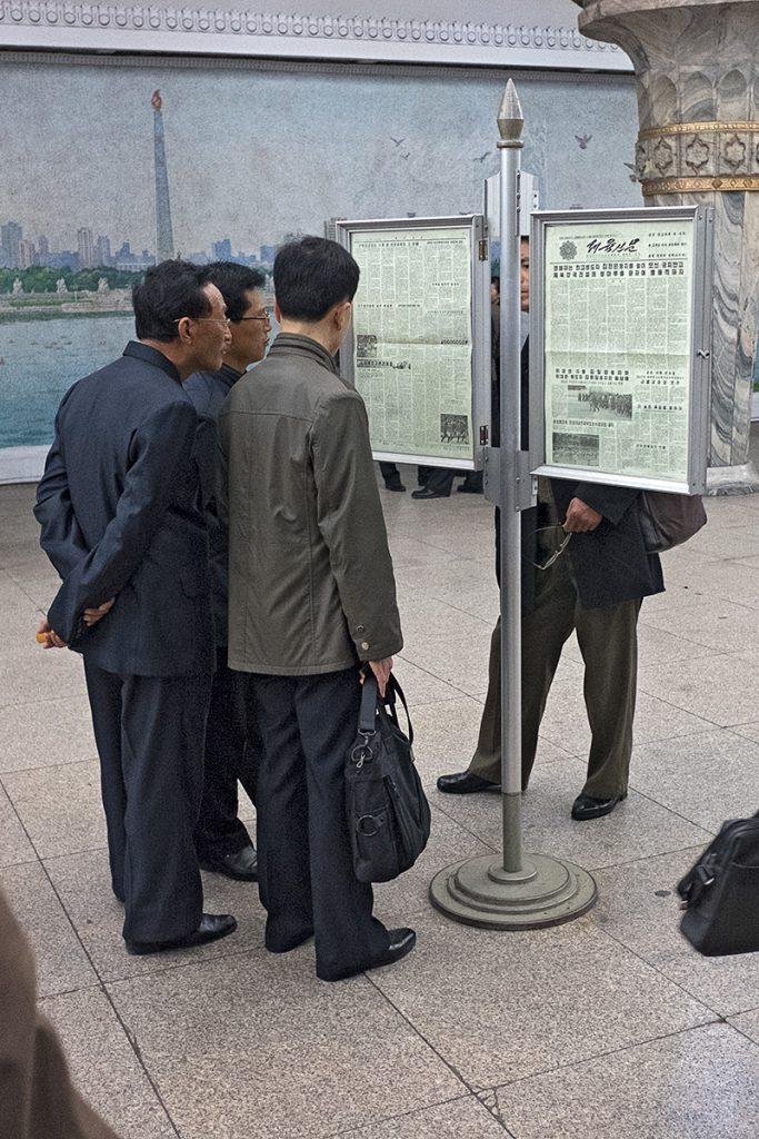 Männer stehen vor Zeitungsständern und lesen die Zeitung.