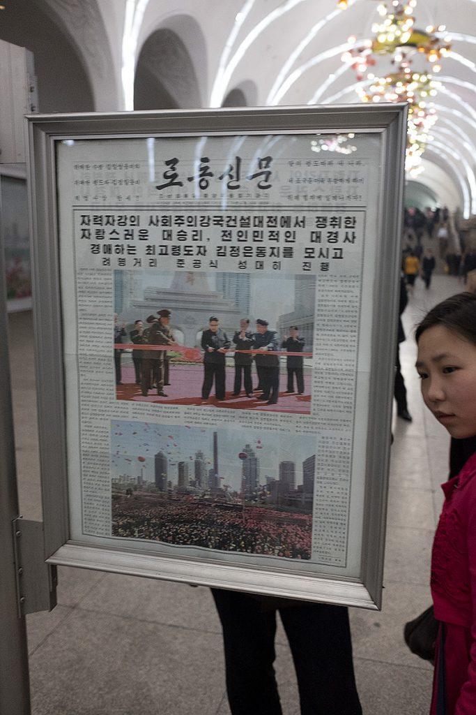 Zeitung in einem Zeitungsständer, rechts eine angeschnittene Leserin.
