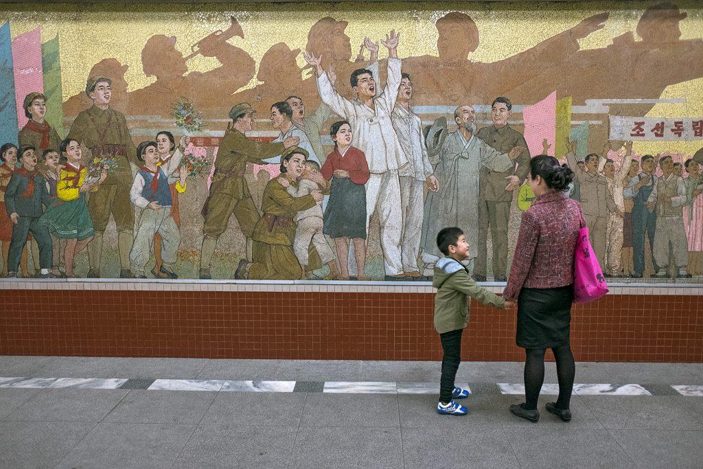 Eine Mutter steht mit ihrem Sohn an der Hand vor einem Mosaikbild mit vielen Menschen.