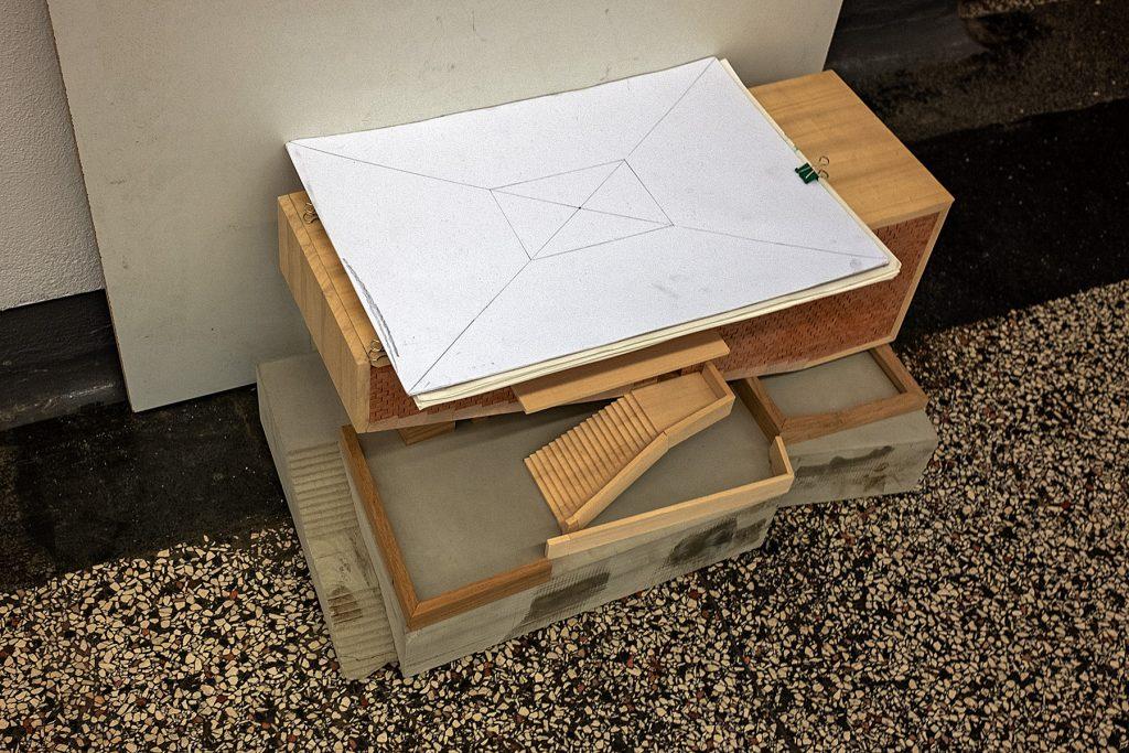 Blick von schräg oben auf ein Architekturmodell auf dem ein Skizzenblock liegt.