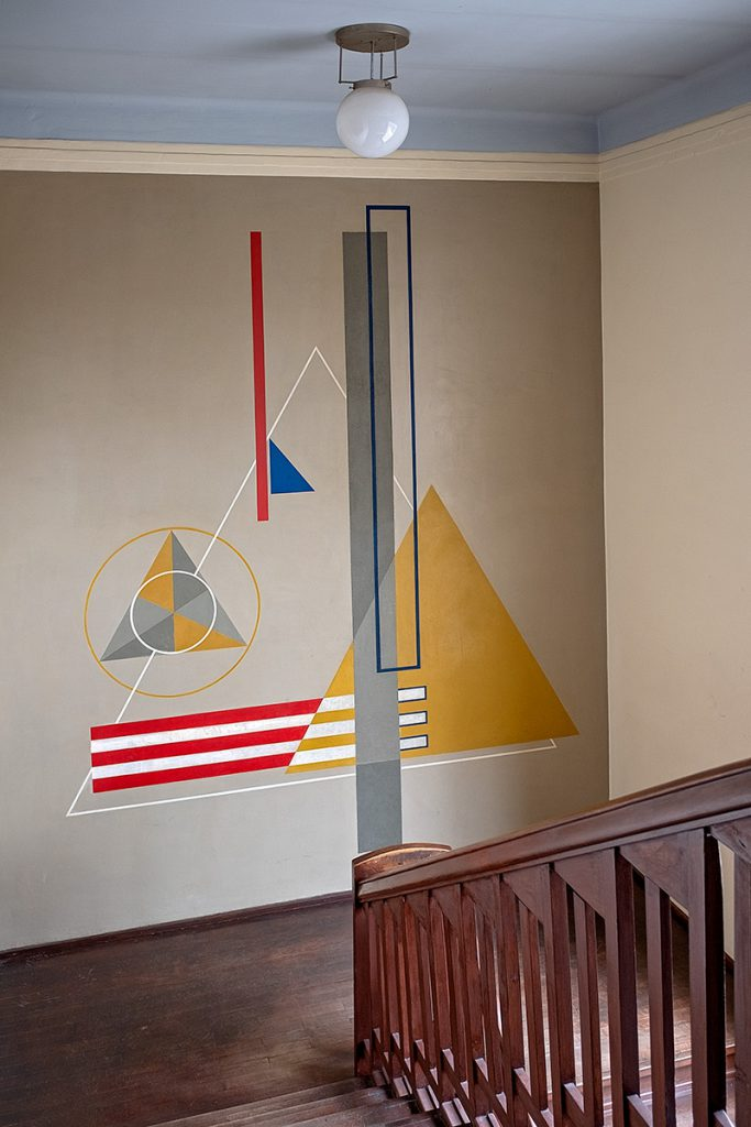 Treppenhaus mit einem Wandbild mit geometrischen Mustern.