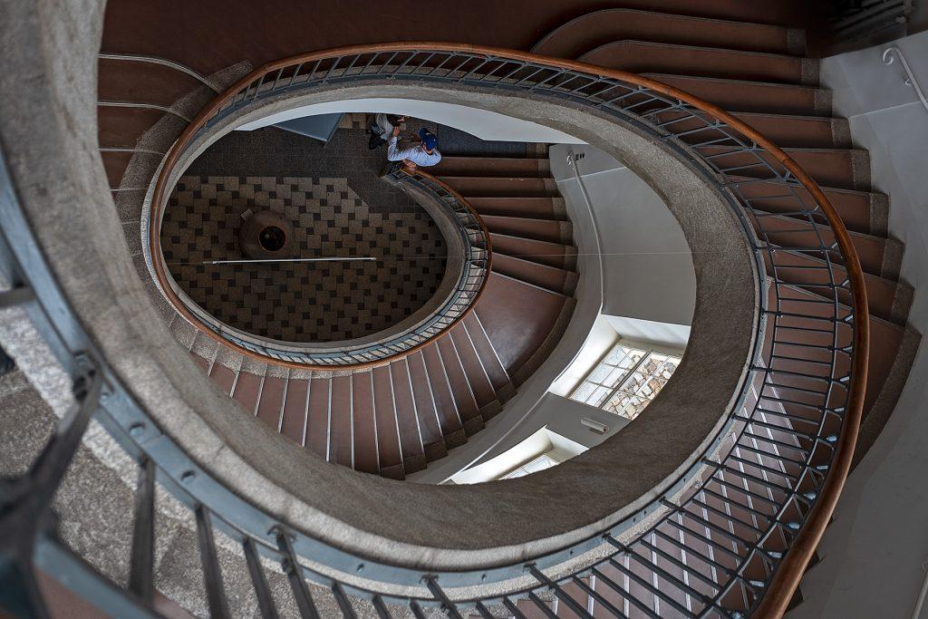 Blick von oben auf eine schneckenförmige Treppe.