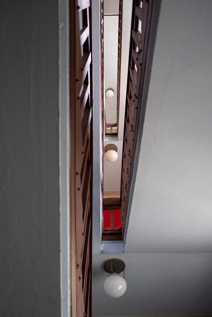 Blick von unten in ein schmales Treppenhaus.