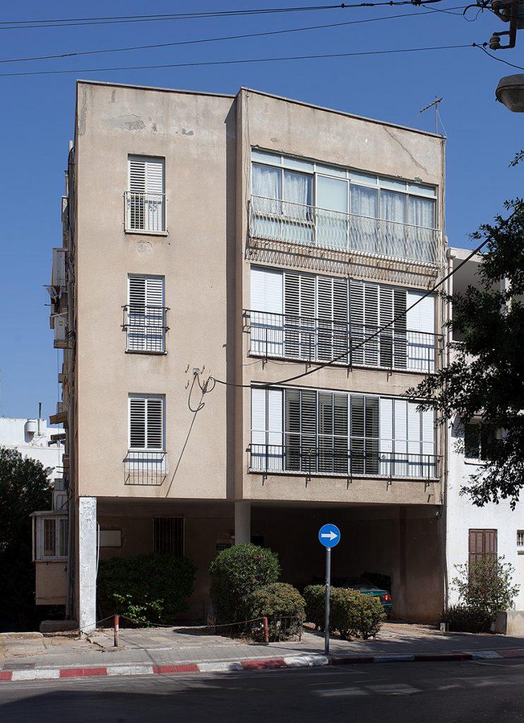 Dreigeschossiges, kubisches Wohnhaus der Moderne auf Pfeilern.