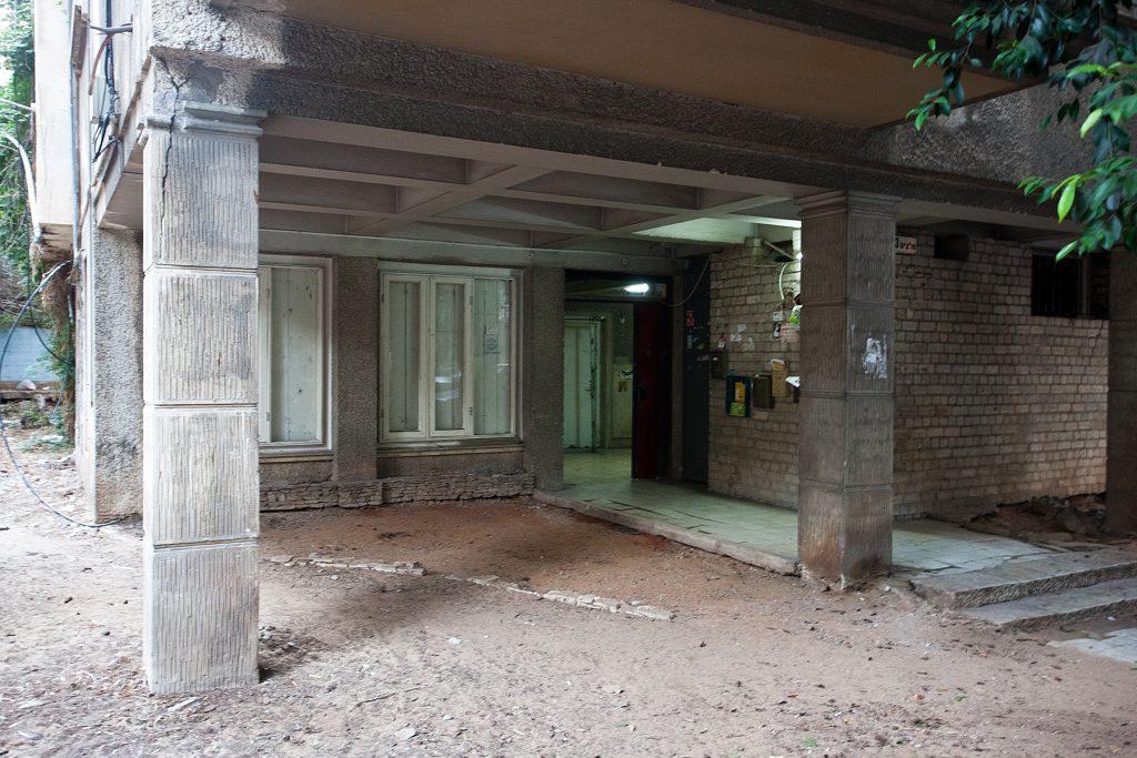 Eingangsbereich eines durch eckige Säulen getragenen Hauses der Moderne.