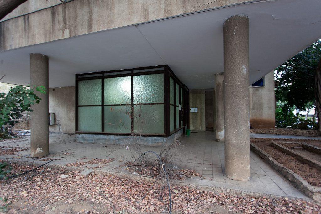 Gläserner Eingangsbereich eines durch runde Säulen getragenen Hauses der Moderne.