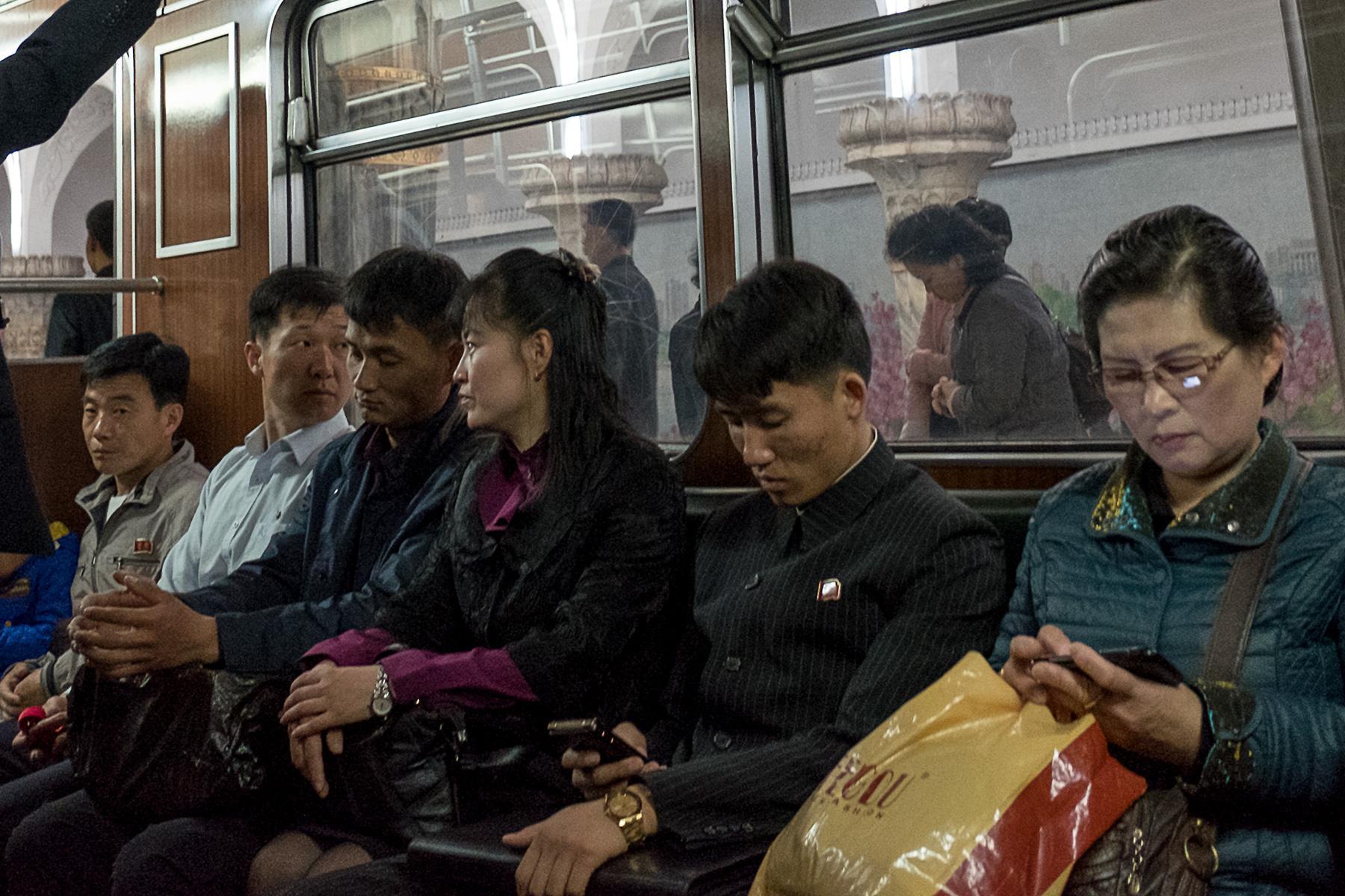 Menschen in der U-Bahn sitzend
