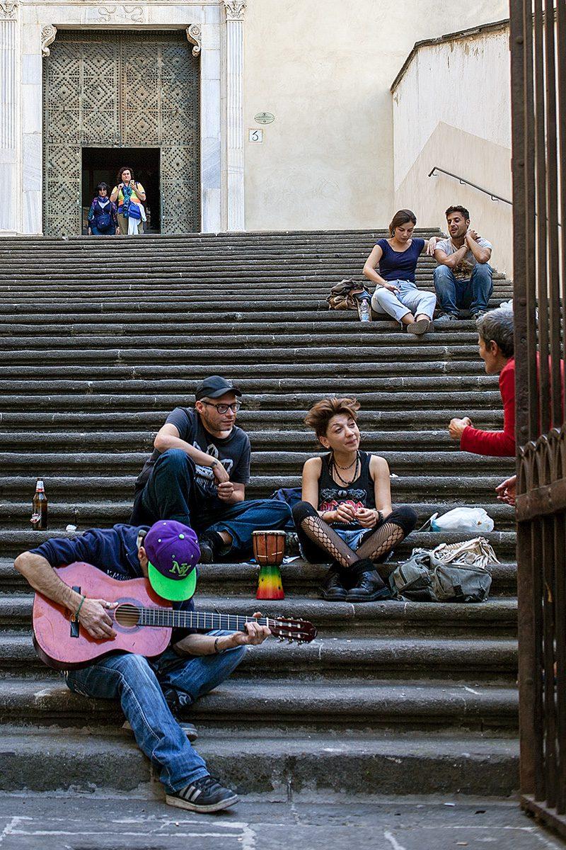 Leute sitzen auf Kirchenstufen, ein Gitarrist spielt