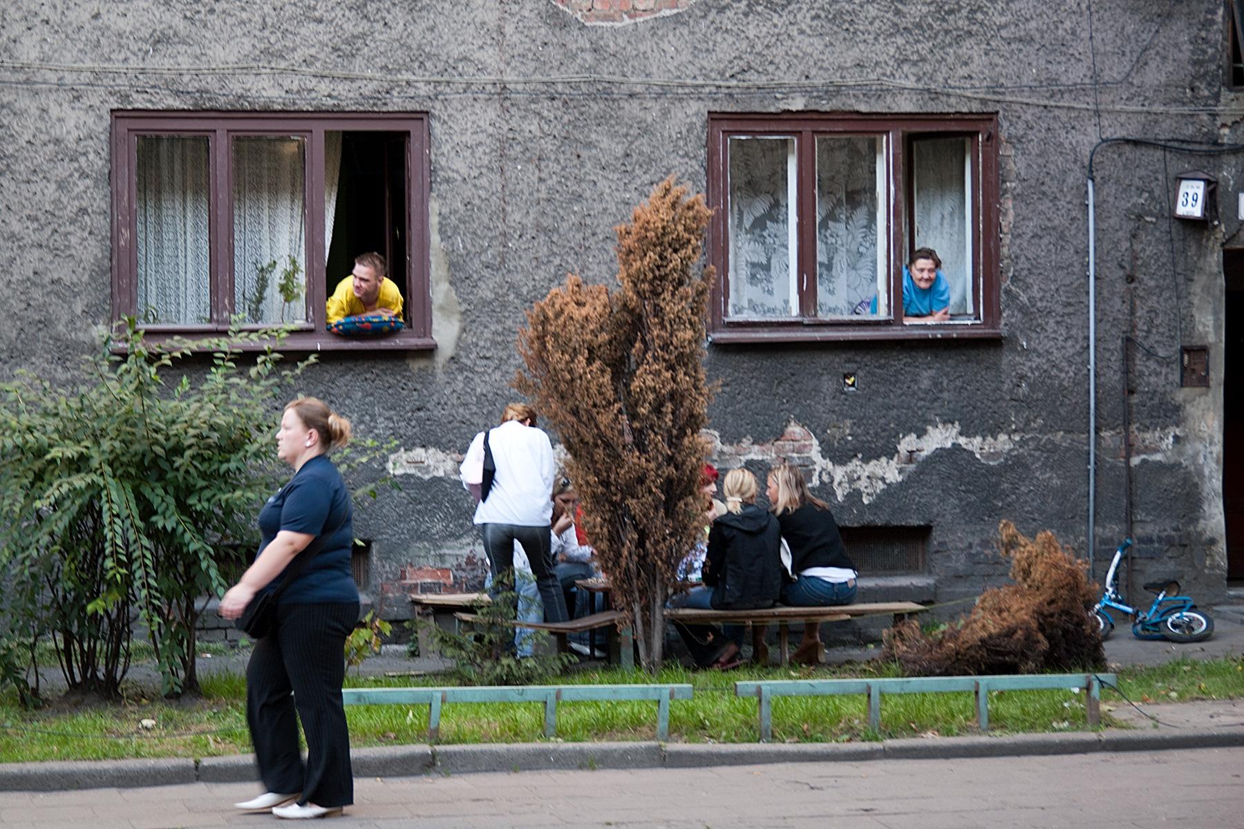 Menschen gucken aus dem Erdgeschossfenster, andere sitzen davor