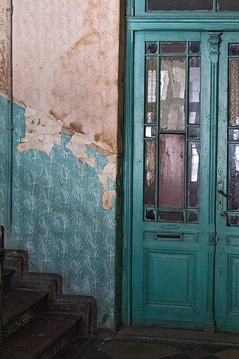Wohnungstür mit gerollten Strukturmustern auf farbiger Wand