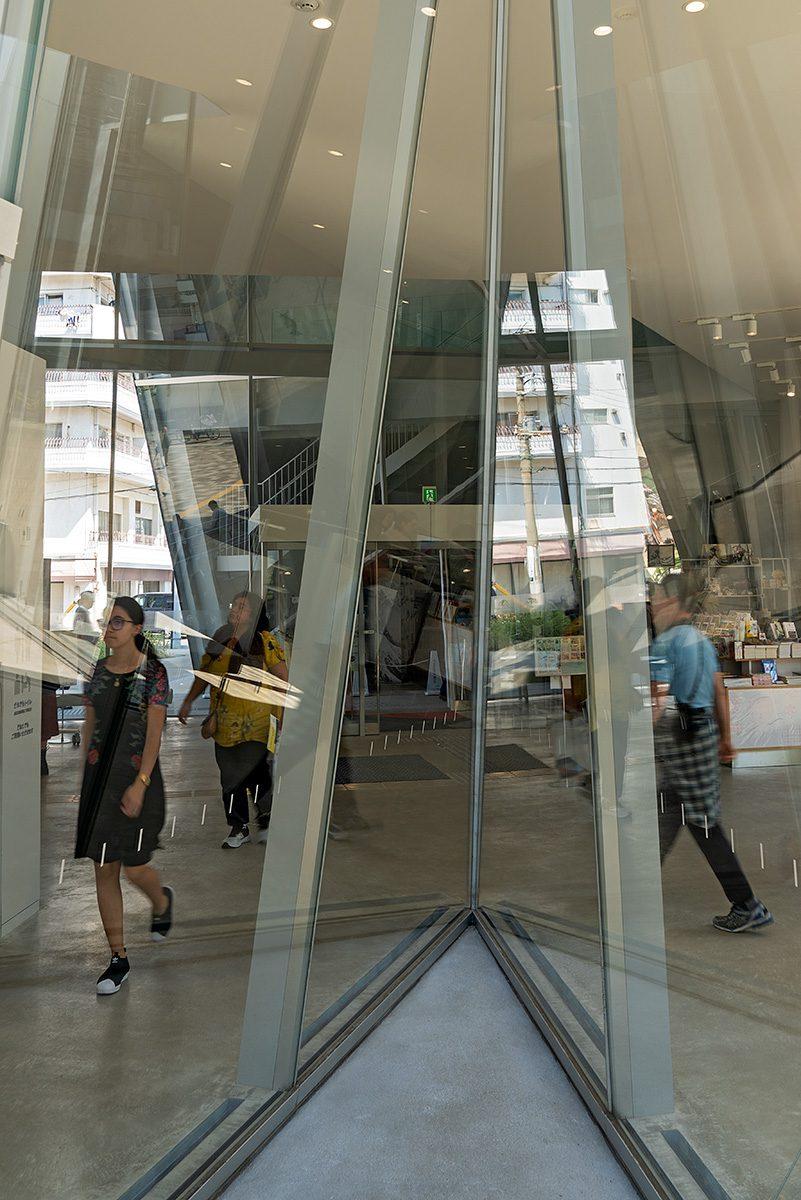 Einblick durch Glas ins Museum mit dahinter gehenden Menschen