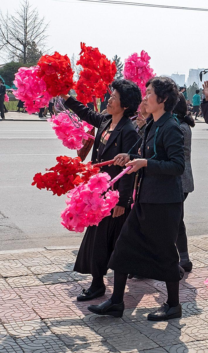 Vorübergehende Menschen mit roten Puscheln in der Hand in Pjöngjang, Nordkorea