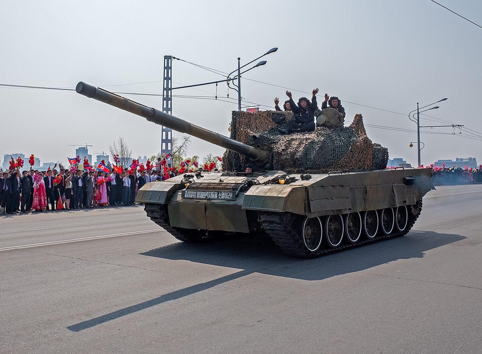 Vorbeifahrender Panzer mit winkenden Soldaten