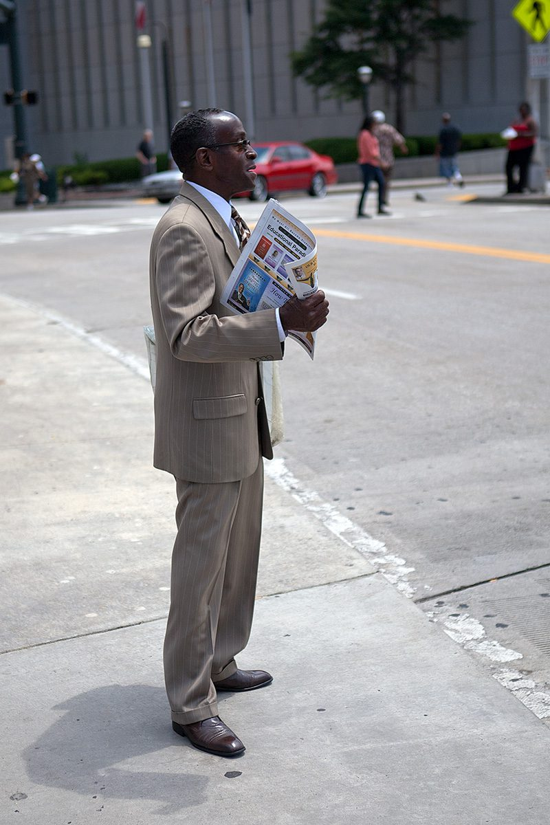 Mann mit Zeitung steht an der Straße