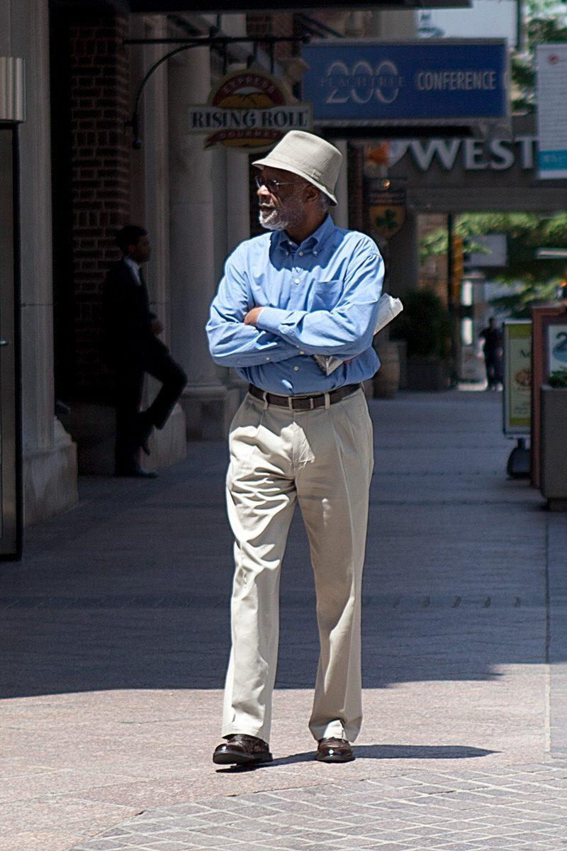 Mann mit Hut geht auf dem Fußweg