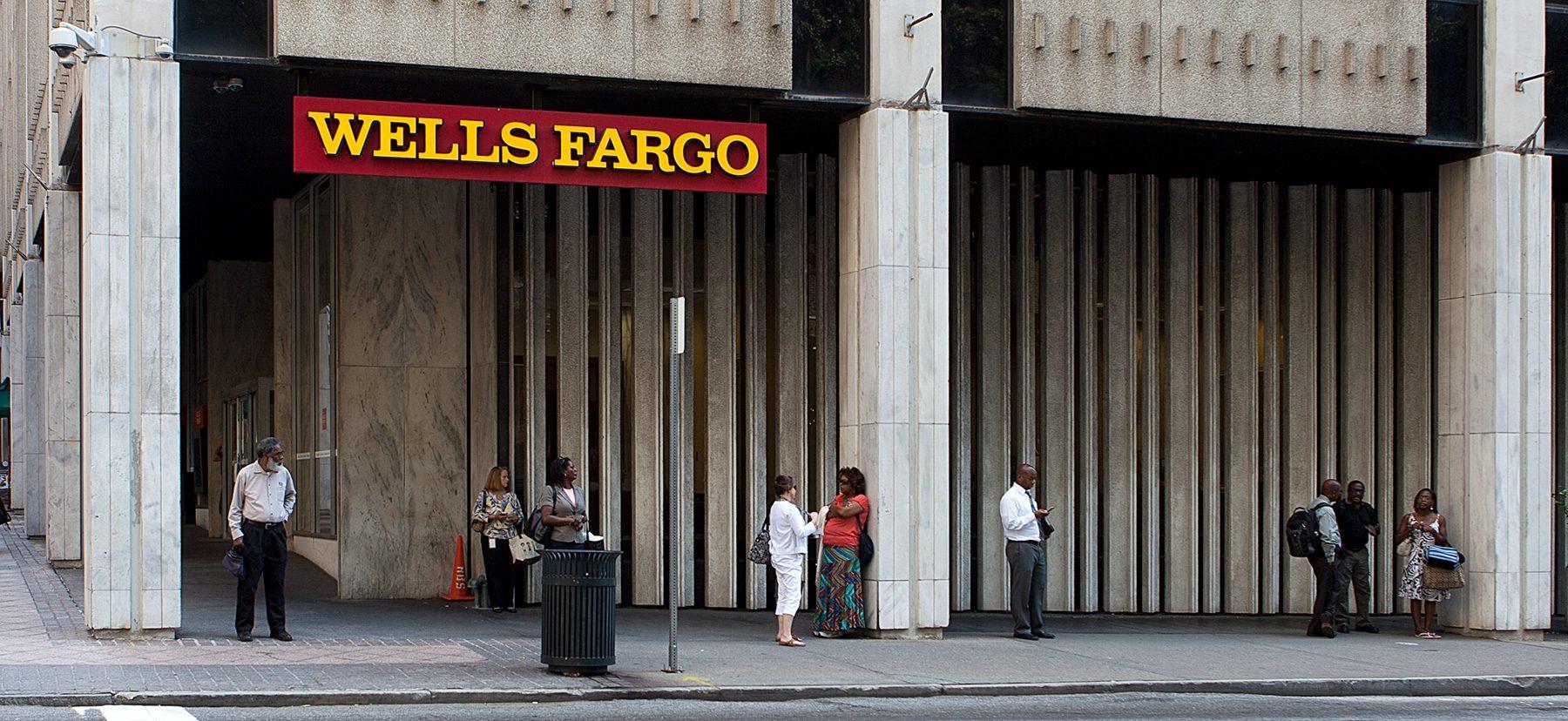 Menschen warten vor Wells Fargo auf den Bus