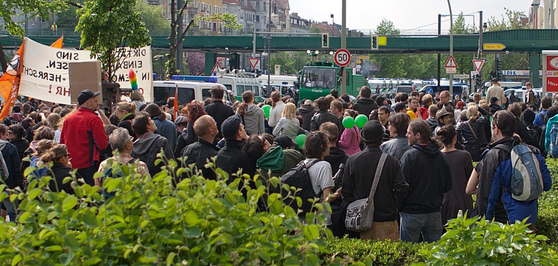 Leute bei einer Blockade vor Polizeifahrzeugen im Beitrag Berlin, 1. Mai