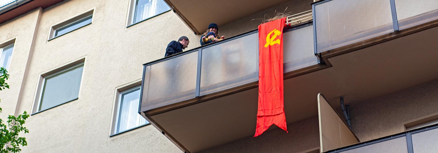 Menschen auf dem Balkon mit sozialistischer Flaggeim Beitrag Berlin, 1. Mai