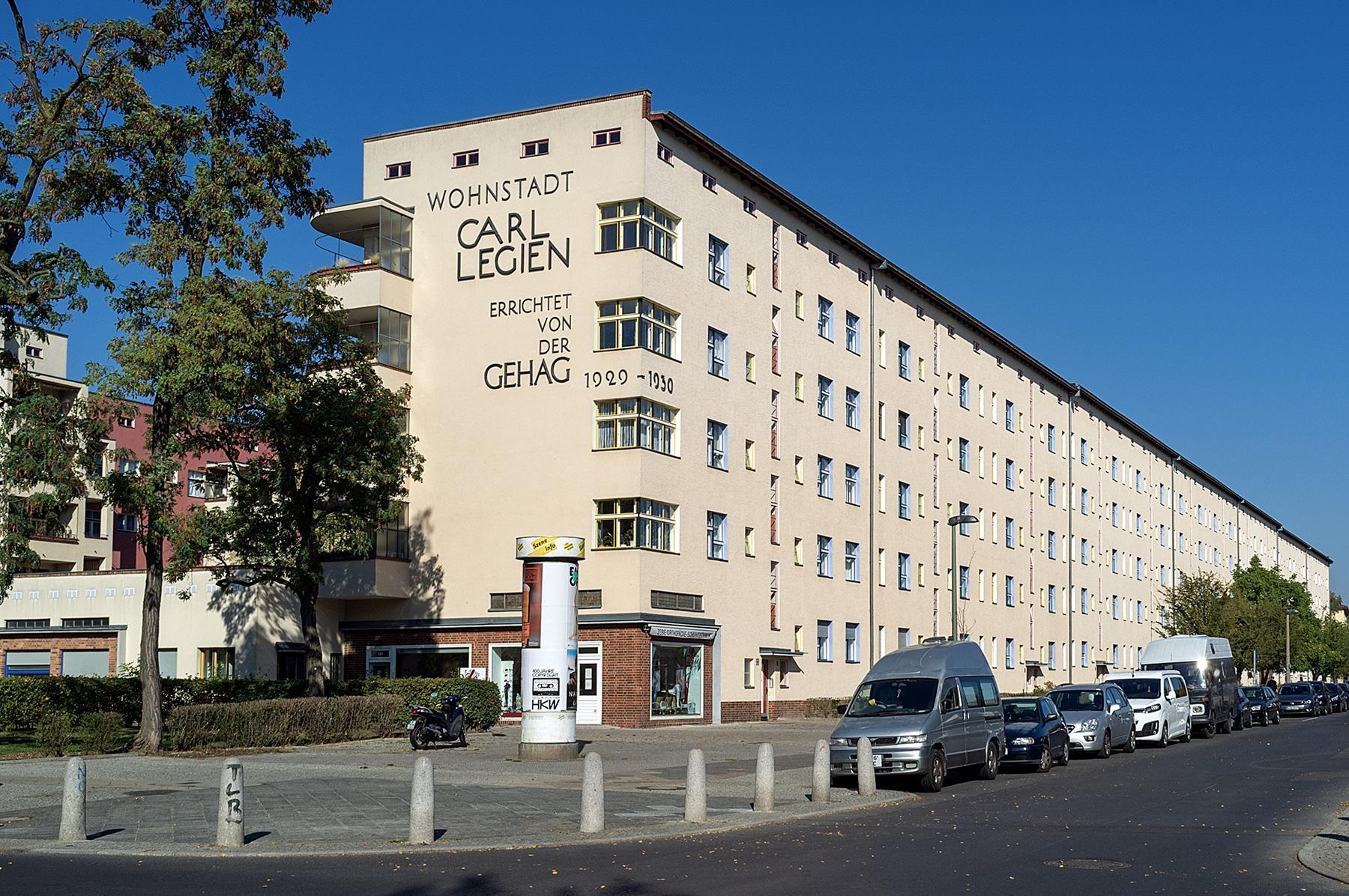 Ein Häuserblock mit der Schrift: Wohnstadt Carl Legien errichtet von dser GEHAG der Siedlung des UNESCO Welterbes