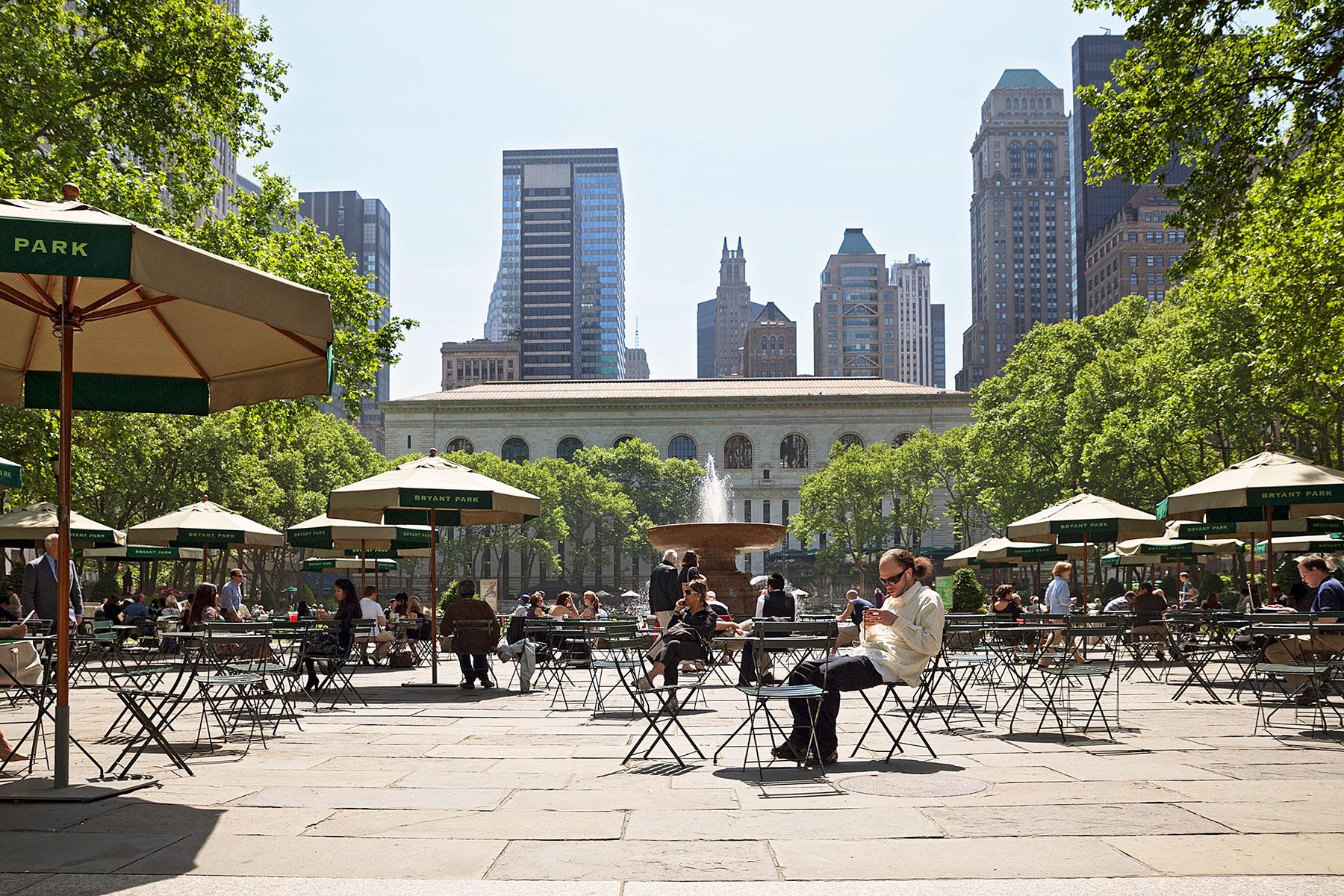 Menschen, die an Tischen sitzen im Bryant Park, Manhattan auf der Seite Stadterkundung.com